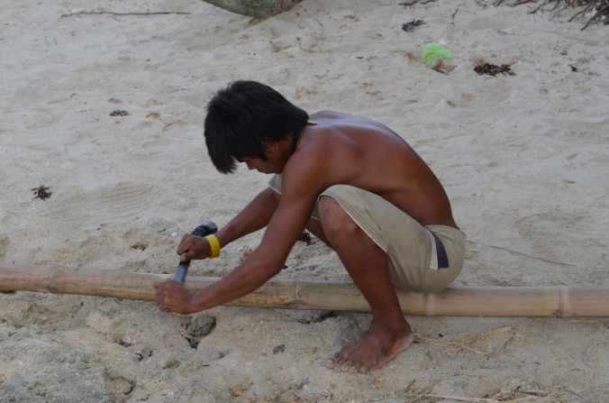 A man carves a piece of wood to be used for a boat.