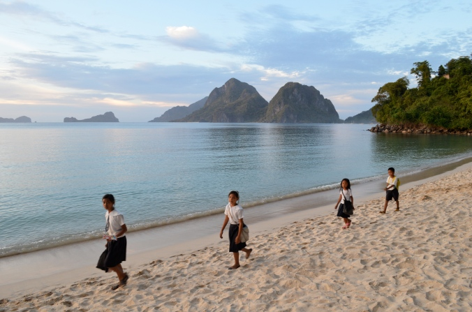 Schoolchildren walk across the beach.