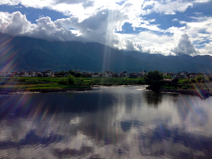 Clouds are reflected in a small pond outside Dali.