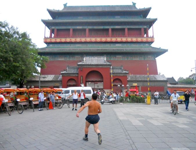 A man prepares to kick a jianzi, or Chinese hacky sack, in front of the Drum Tower.