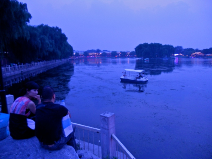 A couple chats at the edge of a lake in Houhai, a popular nightlife destination where many residences have been converted into restaurants and bars.