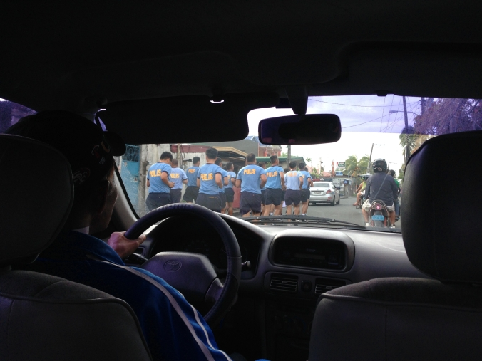 A group of police officers on an early morning run in a small town near Manila.